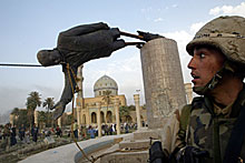 A U.S. soldier watches as a statue of Iraq's President Saddam Hussein falls