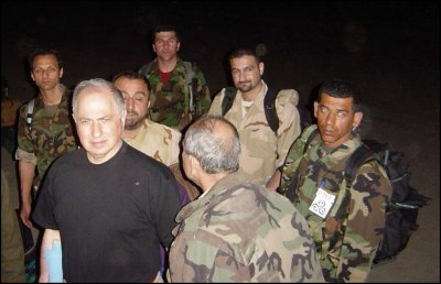 Ahmed Chalabi, left, arrived Sunday at an air base near Nasiriyah in southern Iraq with members of a militia