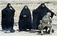 A US female soldier frisks an Iraqi woman