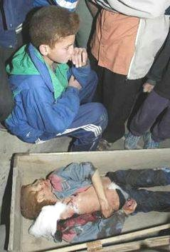 An Iraqi boy sits near the body of his brother